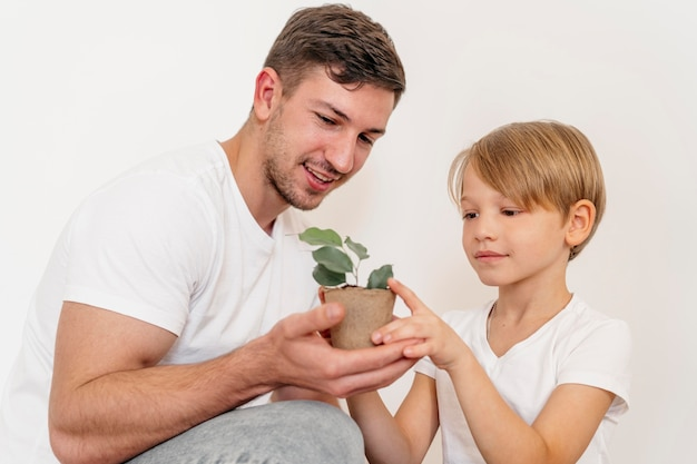 Father and son holding pot of plant and learning about planting Premium Photo