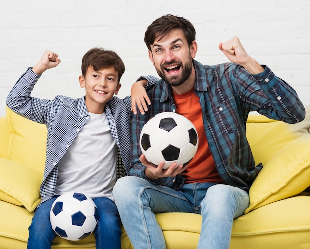 Father and son holding soccer balls Free Photo