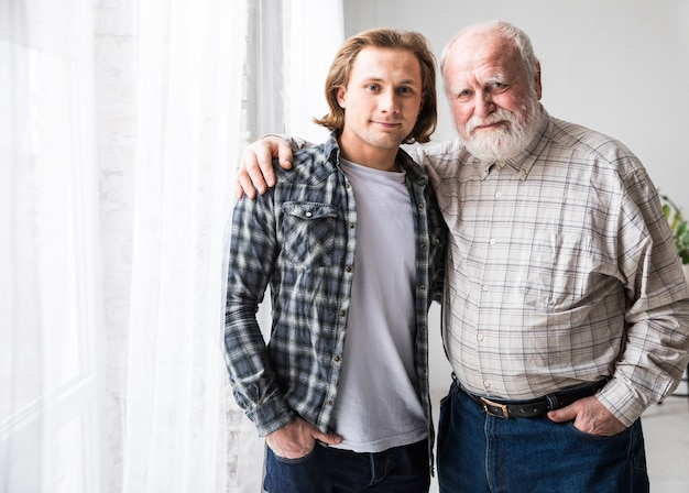 Father and son hugging standing at home Free Photo