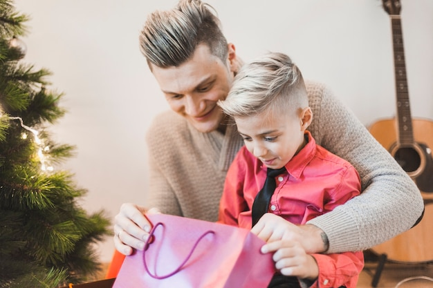 Father and son looking into bag next to christmas tree Free Photo