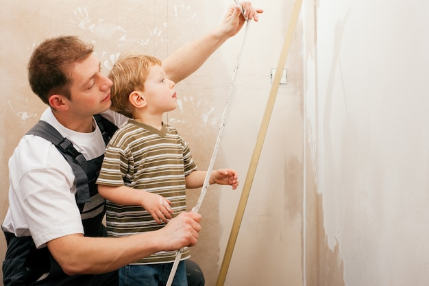 Father and son measuring dry wall Premium Photo