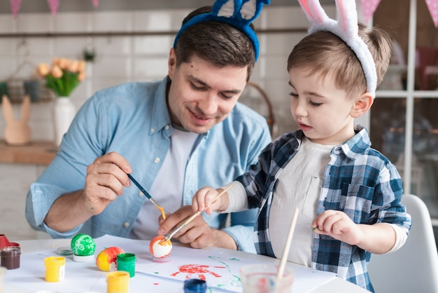 Father and son painting eggs for easter together Free Photo