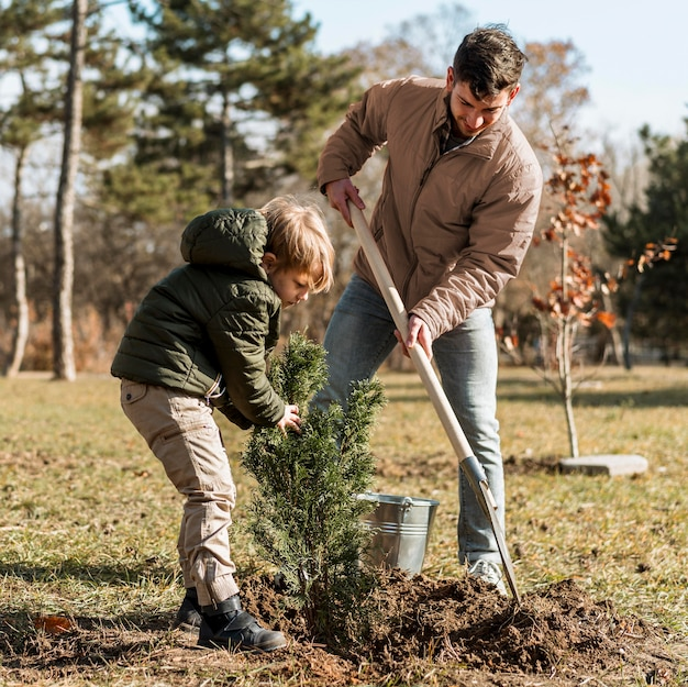 Father and son planting a tree together Free Photo