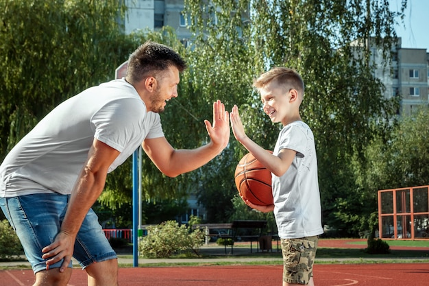 Father and son play basketball together at the basketball court Premium Photo