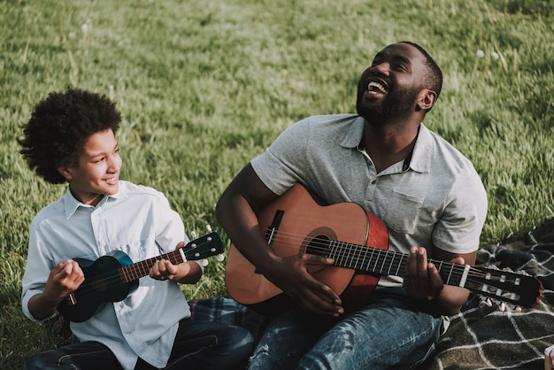 Father and son play on guitars on picnic Premium Photo