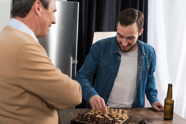 Father and son playing chess Free Photo