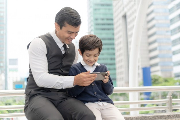 Father and son playing game smart phone together on business district urban Premium Photo