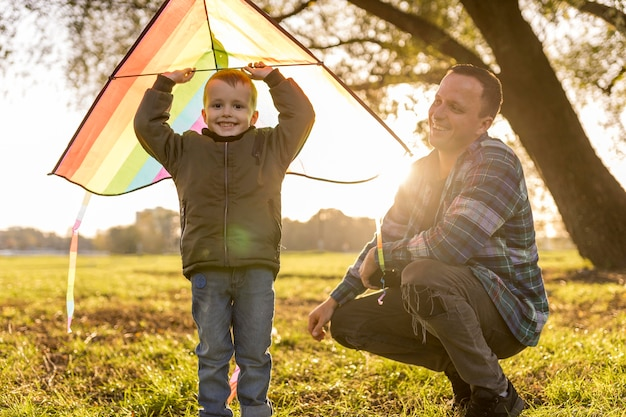 Father and son playing together with a colourful kite Free Photo
