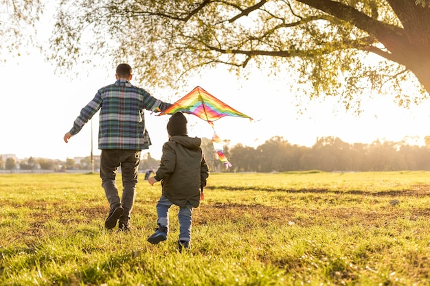 Father and son playing with a kite long view Free Photo