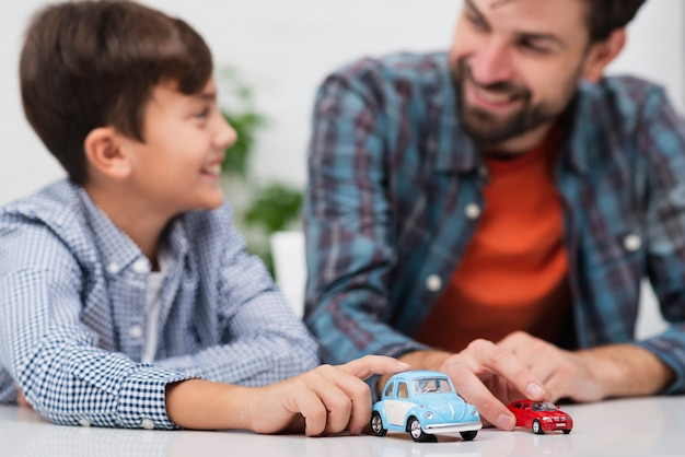 Father and son playing with toy cars and looking at each other Free Photo