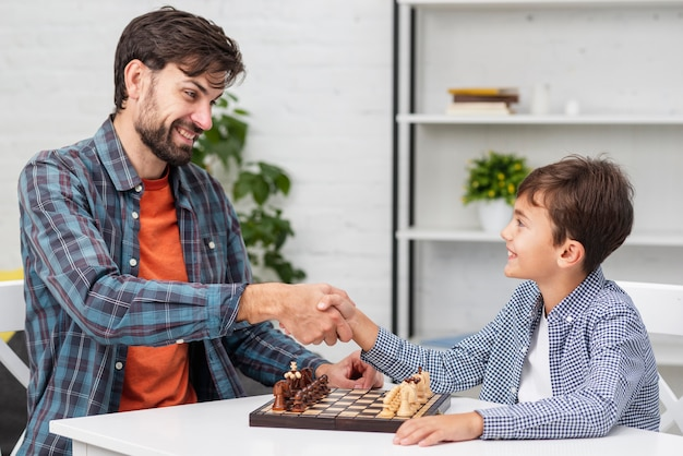 Father and son shaking hands before  chess Free Photo