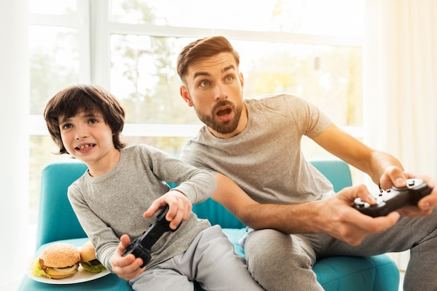 Father and son sitting and playing on console. Premium Photo