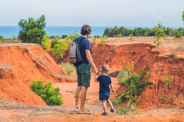 Father and son travelers in red canyon near mui ne, southern vietnam. traveling with children concept. Premium Photo