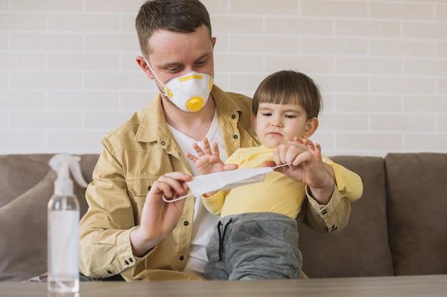 Padre e figlio che usano le maschere mediche Foto Gratuite