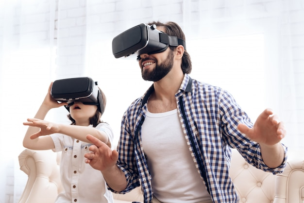 Father and son, using virtual reality glasses, play in game. Premium Photo