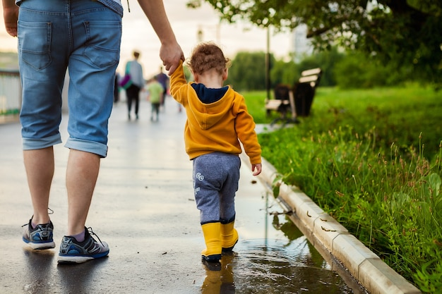 Father and son walking in the fresh air in rubber boots on the puddles after the rain on summer day. Premium Photo