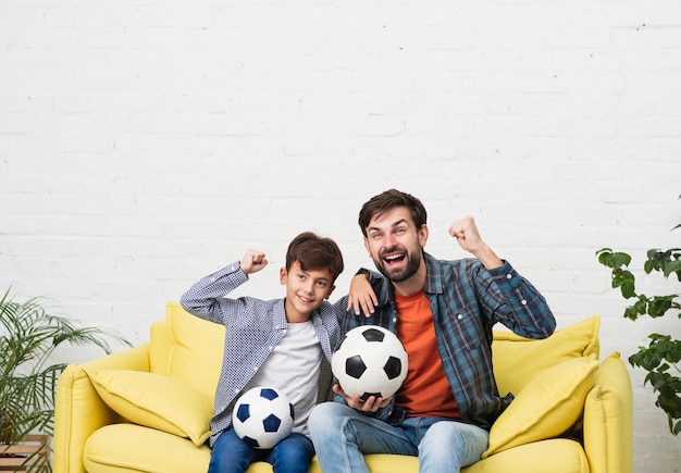 Father and son watching a football match Free Photo