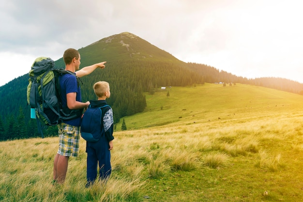 Premium Photo | Father and son with backpacks hiking together at the  mountain