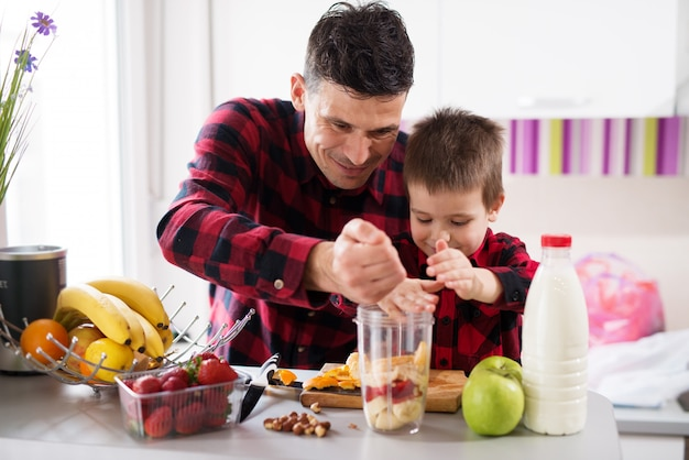 Father and son with joint forces are filling the blender bowl with fruits in bright kitchen. Premium Photo