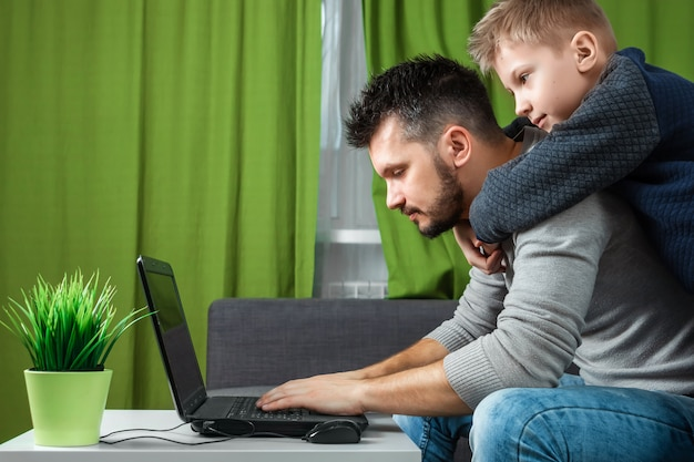 Father and son working on a laptop. Premium Photo