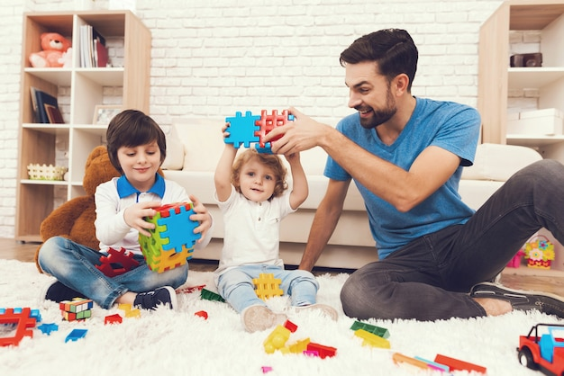 Father and sons is playing with toys. Premium Photo