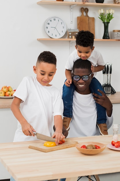 Father and sons preparing dinner together Free Photo