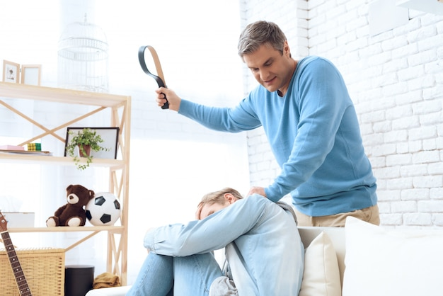 Father swings his belt to hit his son Premium Photo