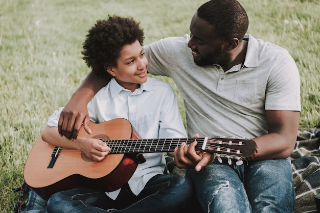 Father teaches his son to play guitar in picnic. Premium Photo