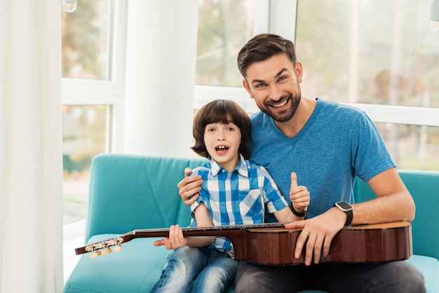 The father teaches his son to play the guitar. Premium Photo