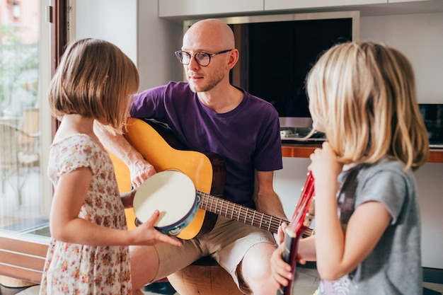 Father teaching to his daughters how to play guitar and playing instruments Premium Photo