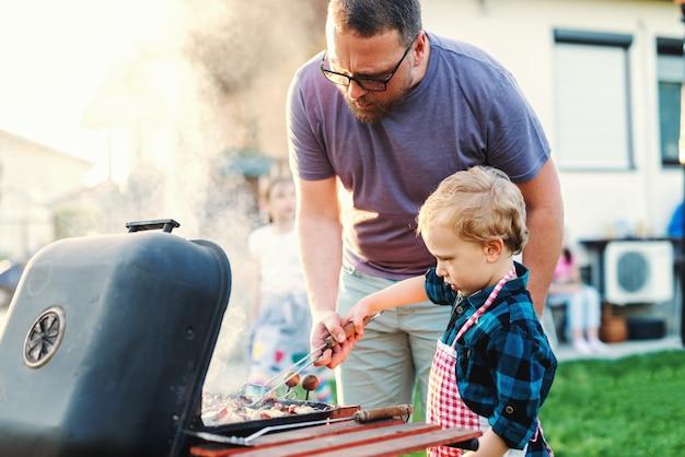 父は彼の幼い息子に夏に裏庭に立っている間グリルする方法を教えました。家族の集まりのコンセプト。 Premium写真