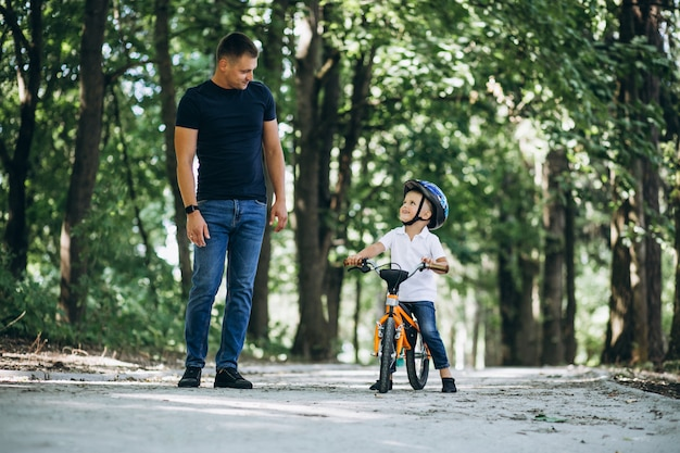Father teaching his little son to ride a bicycle Free Photo
