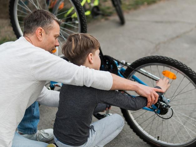 어깨보기를 통해 자전거를 고정 그의 아들을 가르치는 아버지 무료 사진