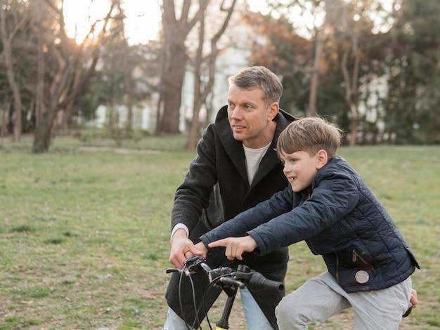 공원에서 자전거를 타는 방법을 아들에게 가르치는 아버지 무료 사진