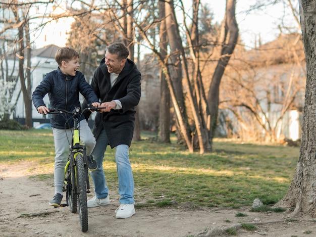 자전거 긴보기를 타고하는 방법 그의 아들을 가르치는 아버지 무료 사진