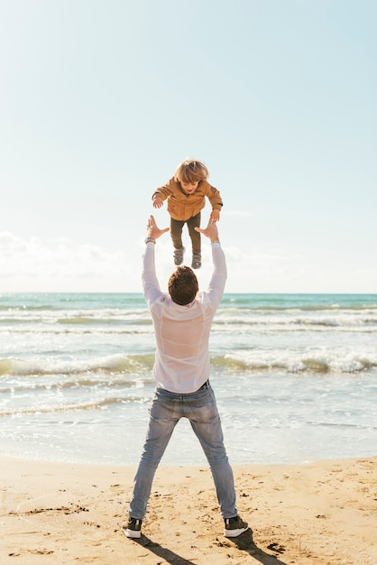 Father throwing laughing child up in sky Free Photo