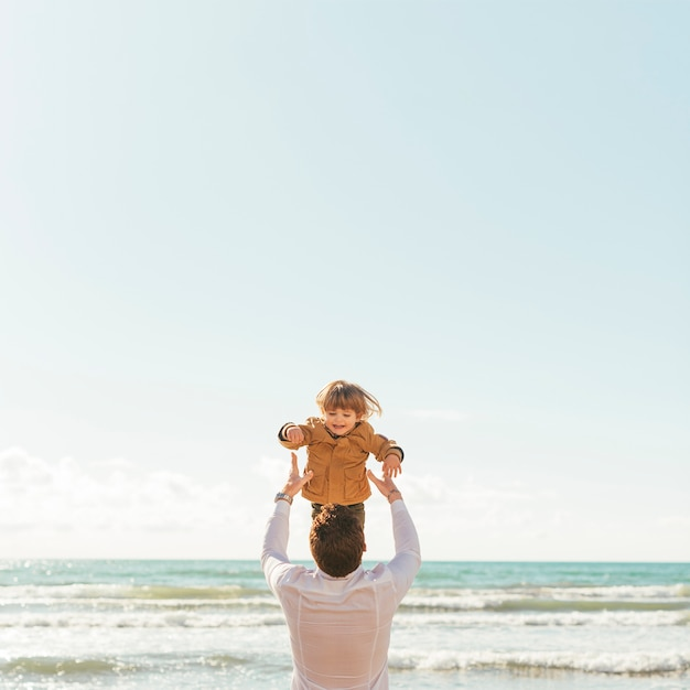 Father throwing laughing toddler up in sky Free Photo