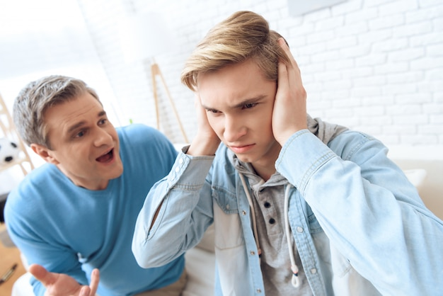 Father tries to talk but son closing his ears Premium Photo