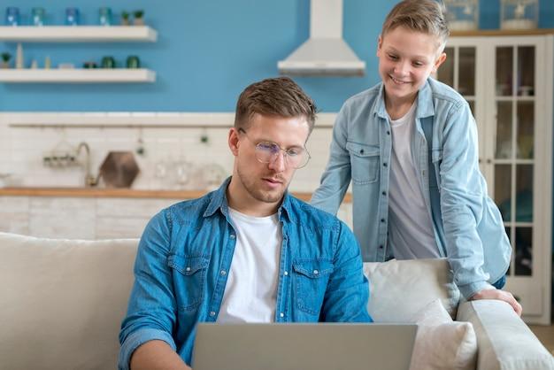 Отец, используя ноутбук и сын смотрит Бесплатные Фотографии