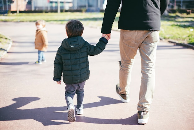 Father walking with son on street Free Photo