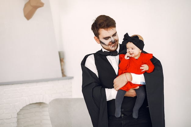 Father with daughter in costumes and makeup. family prepare to celebration of halloween. Free Photo