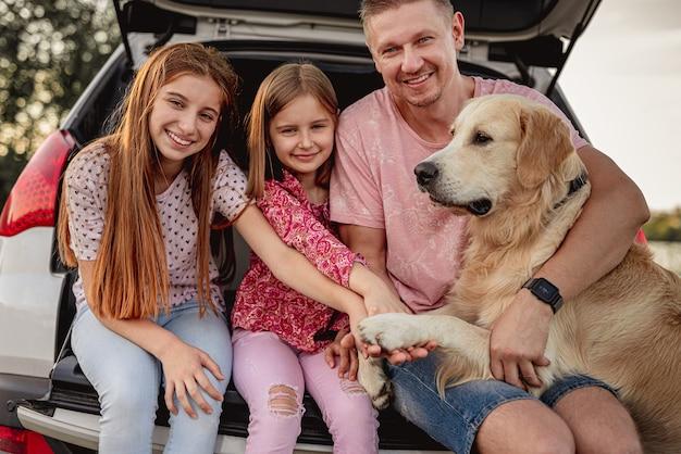 Отец с дочерьми и золотистый ретривер, сидя в багажнике автомобиля на природе Premium Фотографии