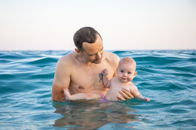 Отец с дочерью плавают и отдыхают в море во время заката Premium Фотографии