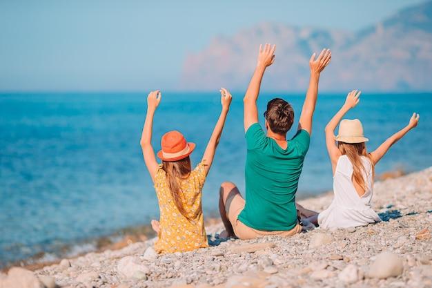 Отец с детьми на пляже, наслаждаясь летом Premium Фотографии