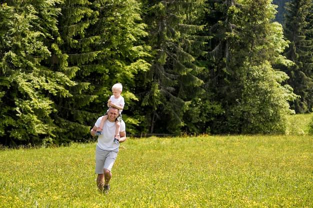 Father with little son on shoulders walking on a green meadow Premium Photo