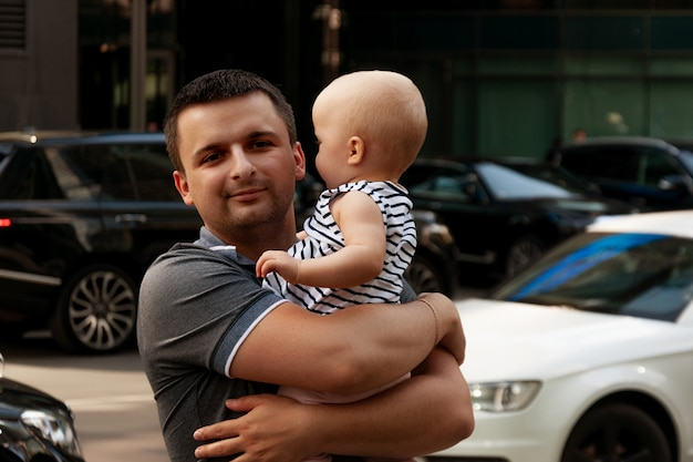 Father with one year old baby in his arms. walk in an urban environment. Premium Photo