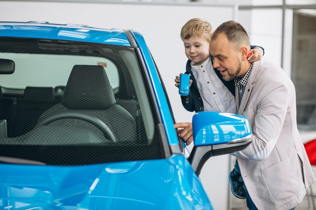Father with son looking at a car in a car showroom Free Photo