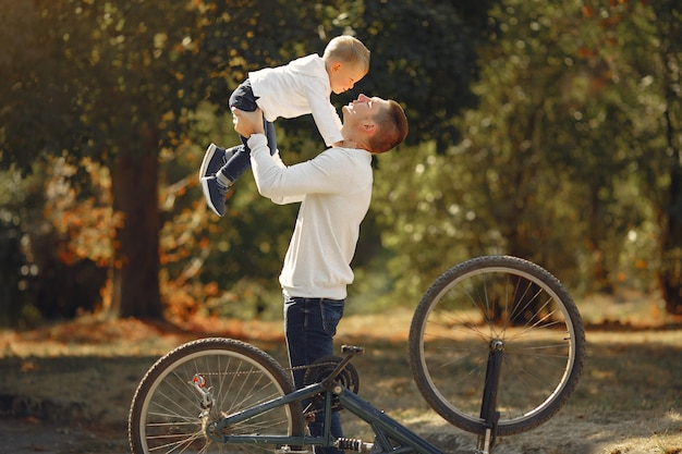 Father with son repare the bike in a park Free Photo