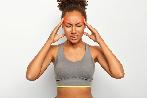 Fatigue overworked afro american woman massages temples, feels strong headache, closes eyes with pain, suffers from migraine, dressed in sport bra, clenches teeth, isolated on white wall Free Photo