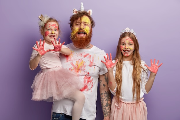 Fatigue redhead bearded dad smeared with yellow and red watercolors Free Photo